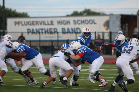 Senior Rashad Carter hands the ball of to Junior Xavier Dotson. Senior Riley Wells blocks nose tackle.