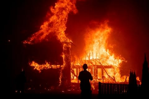 A fireman stands in front of a burning building.