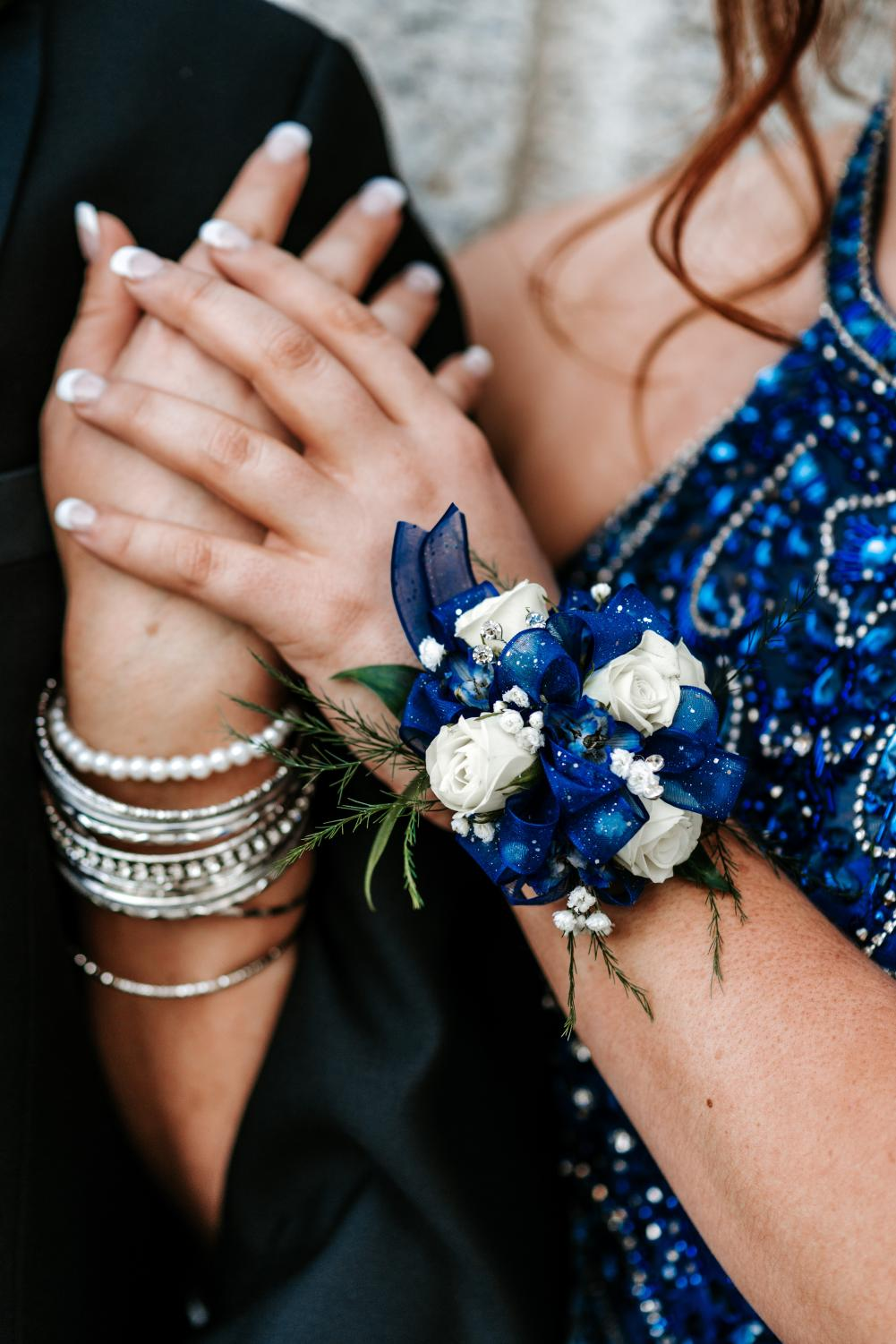 Corsages and Boutonnieres  come from a tradition when flowers were worn to make one smell nice while dancing with their partner. Today, they are used as accessories to go with the dress or tuxedo.