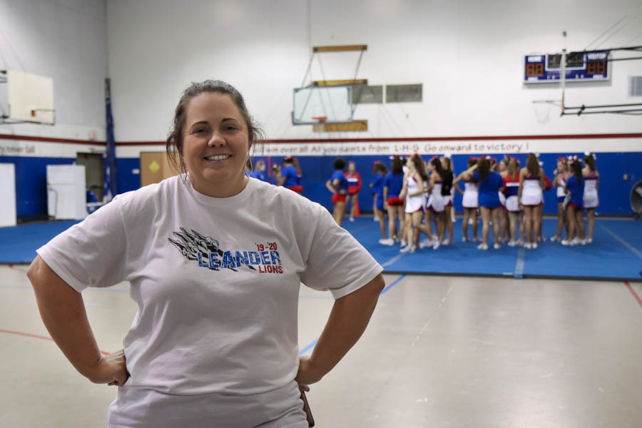 On Sept. 19, varsity cheer coach Amber Hall poses in front of her cheer squad.
