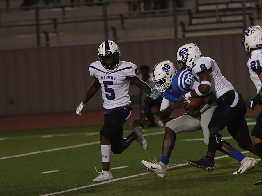 On Sept. 20, senior Keon Leonard runs with the ball while getting tackled by a Cedar Ridge Raider.