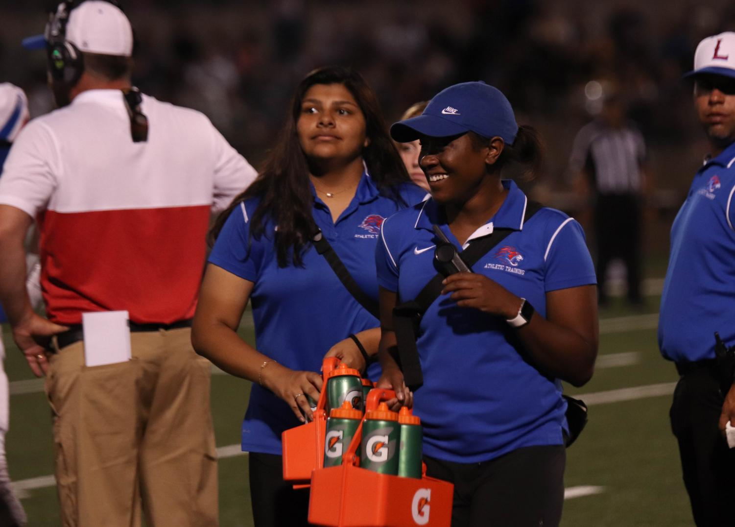 On Aug. 13, athletic trainer Aerin Henderson helps out on the field during a varsity football game against Stony Point.