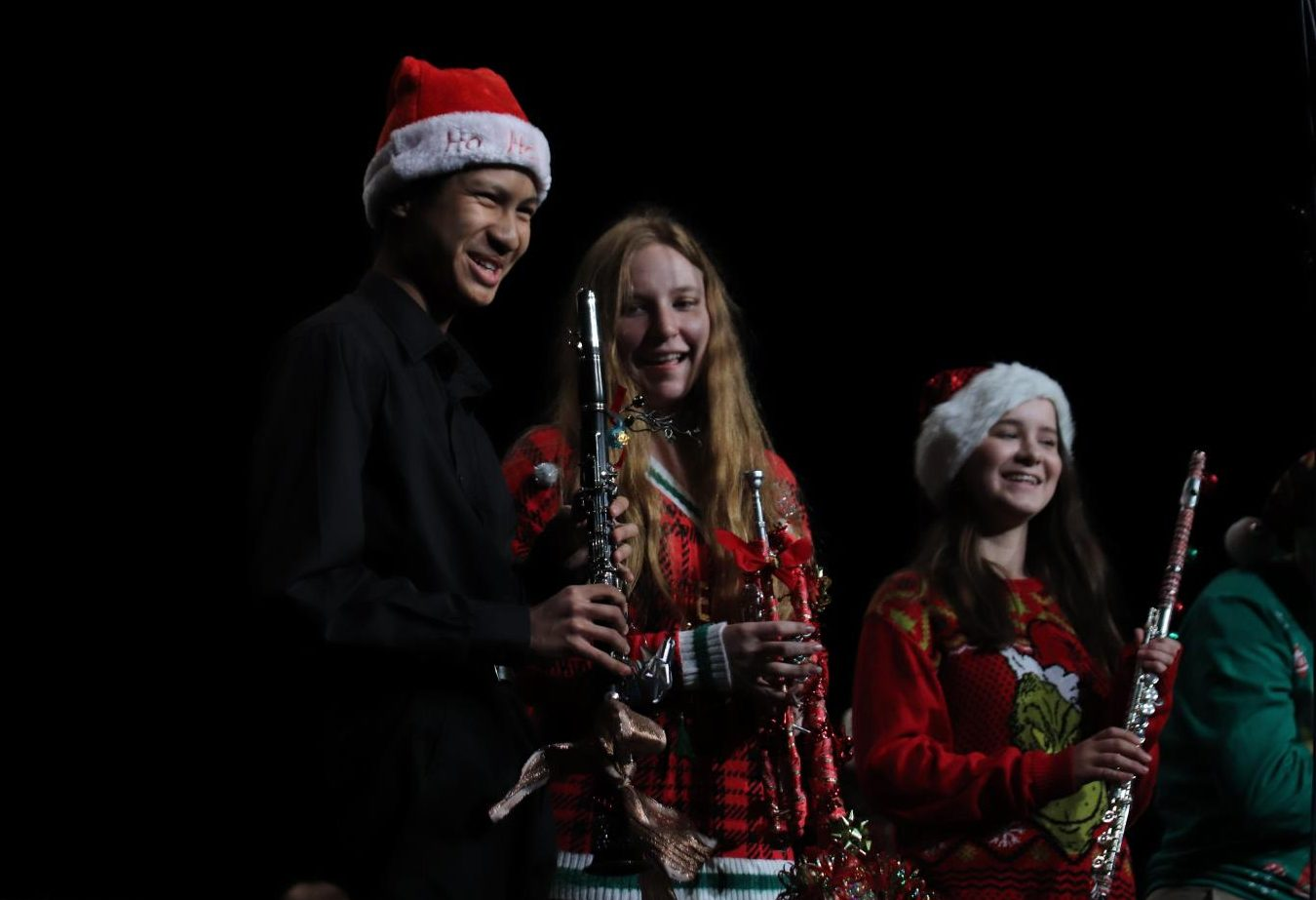 Sophomore Ngyugen Ngyugen, freshman Elizabeth Unger and junior Ashley Snyder pose with their decorated instruments in their ugly sweaters at the Winter Concert.