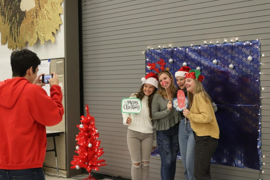 Senior Alexa Cummings, senior Chloe Albrecht, junior Addison Porch and junior Mia Evans pose at the IB Winter Social on Dec. 12.
