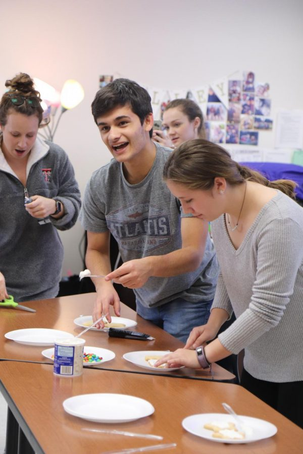 Senior Alex Oveisi decorates a cookie at yearbooks cookie decorating competition.